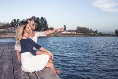 Härliga unga flickor som tycker om bredvid floden arkivfoto