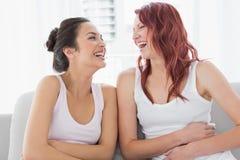Härliga unga kvinnliga vänner som skrattar i vardagsrum Arkivbild