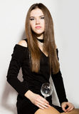 Härliga unga kvinnor för modeaffär i lite svart klänning med tillbehör som rymmer ett tomt vinexponeringsglas Royaltyfria Foton