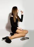 Härliga unga kvinnor för modeaffär i lite svart klänning med tillbehör som rymmer ett tomt vinexponeringsglas Arkivfoto