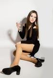 Härliga unga kvinnor för modeaffär i lite svart klänning med tillbehör som rymmer ett tomt vinexponeringsglas Arkivbilder