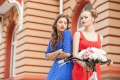 Härliga unga kvinnor går över stad royaltyfria bilder