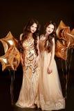Härliga unga kvinnor i elegant guld- klänning över guld- stjärna b Fotografering för Bildbyråer
