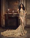 Härliga unga kvinnor i guld- klänning royaltyfria bilder