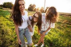 Härliga unga kvinnor i iklädd solglasögon den trevliga kläderna står, i fältet och att le på en solig dag fotografering för bildbyråer