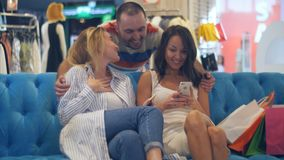 Härliga unga kvinnor med shoppingpåsar och smartphone i gallerian som möter deras manliga vän Royaltyfri Bild