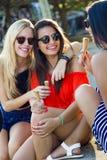 Härliga unga kvinnor som har gyckel med glass på parkera Arkivfoto