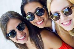 Härliga unga kvinnor som har gyckel på parkera Royaltyfri Foto