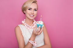 Härliga unga kvinnor som rymmer den lilla kakan med den färgrika stearinljuset Födelsedag ferie royaltyfria bilder