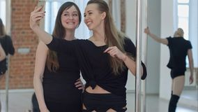 Härliga unga kvinnor som tar en selfie under ett avbrott på en polkonditiongrupp Arkivfoto