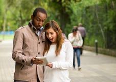 Härliga unga mång--person som tillhör en etnisk minoritet par som har gyckel tillsammans på parkera, par som håller ögonen på han Arkivfoto