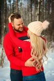 Härliga unga par i vintern i träna, kram, lycklig romans arkivfoton
