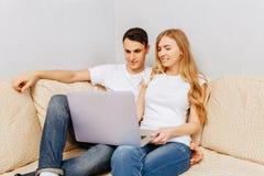 Härliga unga par, man och kvinna som använder en bärbar dator, att krama och att le som hemma sitter på soffan arkivfoto