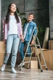 härliga unga par med askar och stege som flyttar sig in i arkivbilder