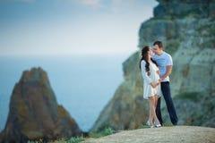 Härliga unga par som förväntar, behandla som ett barn att posera på bergsikt med det blåa havet som bakgrund royaltyfri foto