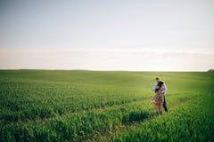 Härliga unga par som kramar försiktigt i solsken i vårgräsplanfält Lycklig familj som omfamnar i grön äng med nytt gräs arkivfoto