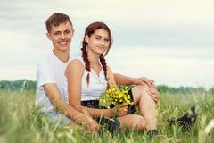 Härliga unga par som kramar i fältet med blommor i solen, begreppet av ett förälskelseförhållande arkivfoto