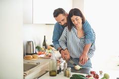 Härliga unga par som tillsammans hemma lagar mat royaltyfri foto