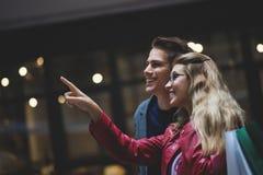 Härliga unga par som tillsammans tycker om i shopping och att ha gyckel Consumerism förälskelse som daterar, livsstilbegrepp