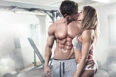Härliga unga sportiga kyssande sexiga par i idrottshall Arkivbild