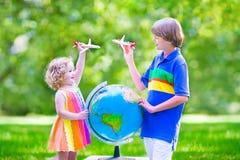 Härliga ungar som spelar med flygplan och jordklotet Arkivbilder