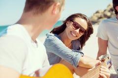 Härliga ungdomarmed gitarren på stranden Arkivfoton
