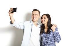 Härliga upphetsade unga raka par som gör roliga framsidor, skrattar, ler & tar selfie och att ha gyckel med den mobila mobiltelef arkivfoto