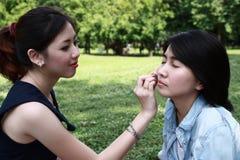 härliga vänflickor hjälpa makeup som är deras till Arkivfoton