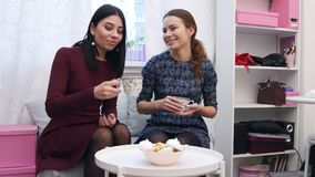 Härliga vänner för unga kvinnor som dricker te i klädervisningslokal efter shoppingen stock video