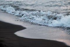 Härliga vågor av havet skummar på en sandig kust Arkivbilder