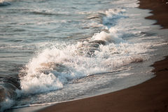 Härliga vågor av havet skummar på en sandig kust Royaltyfria Bilder