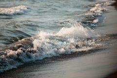 Härliga vågor av havet skummar på en sandig kust Arkivfoton