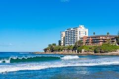 Härliga vågor och strandbyggnader på solig dag Arkivfoto