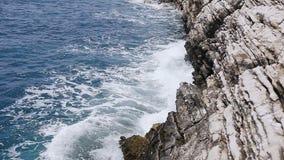 Härliga vågor som plaskar på i lager, vaggar klippan på Petrovac Montenegro Adriatiskt hav Havsvågor stänker vaggar lager videofilmer