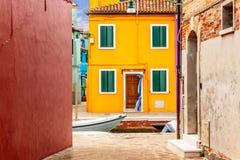Härliga vibrerande färgrika hus i Burano med den smala gatan nära Venedig i Italien arkivbilder