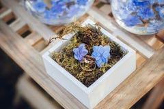 Härliga vigselringar i vita träaskar med blåa små blommor ro för pärla för inbjudan för garnering för dekor för bakgrundsboutonni Royaltyfri Foto