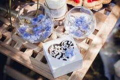 Härliga vigselringar i vita träaskar med blåa små blommor ro för pärla för inbjudan för garnering för dekor för bakgrundsboutonni Arkivfoton