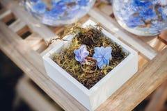 Härliga vigselringar i vita träaskar med blåa små blommor ro för pärla för inbjudan för garnering för dekor för bakgrundsboutonni Royaltyfri Fotografi
