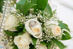 Härliga vita bröllopbuketter i rosa vigselringar för korgbukettblommor royaltyfria foton