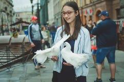Härliga vita duvor sitter på händerna av en turist- flicka royaltyfri foto