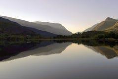 Härliga walesiska berg reflekterade i lugna vatten av sjön Llyn Padarn, Llan Beris Wales royaltyfri foto