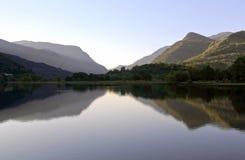 Härliga walesiska berg reflekterade i lugna vatten av sjön Llyn Padarn, Llan Beris Wales royaltyfri fotografi