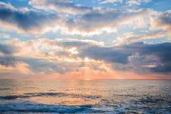 härligt över havssoluppgång Solstrålavbrott till och med molnen Arkivfoto