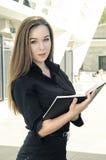 Härligt affärskvinnaanseende på byggnadsbakgrunden med notepaden Arkivfoto