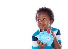 Härligt afroamerican barn med en blå moneybox Arkivfoto