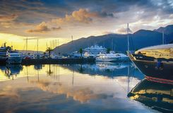 Härligt aftonlandskap med yachter, guld- moln och reflexioner i vatten Montenegro Tivat, marina Porto Montenegro Fotografering för Bildbyråer