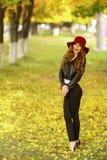 Härligt anseende för elegant kvinna i trendig röd hatt i en parkera i höst Fotografering för Bildbyråer