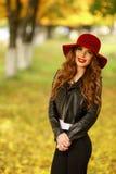 Härligt anseende för elegant kvinna i trendig röd hatt i en parkera i höst Royaltyfria Bilder