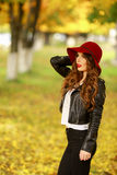 Härligt anseende för elegant kvinna i trendig röd hatt i en parkera i höst Royaltyfri Fotografi