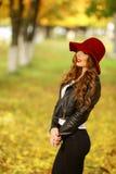 Härligt anseende för elegant kvinna i trendig röd hatt i en parkera i höst Arkivbilder